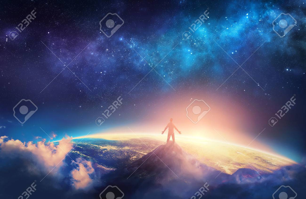 A man climbs a high mountain and lifts his arms up in praise - 74918940