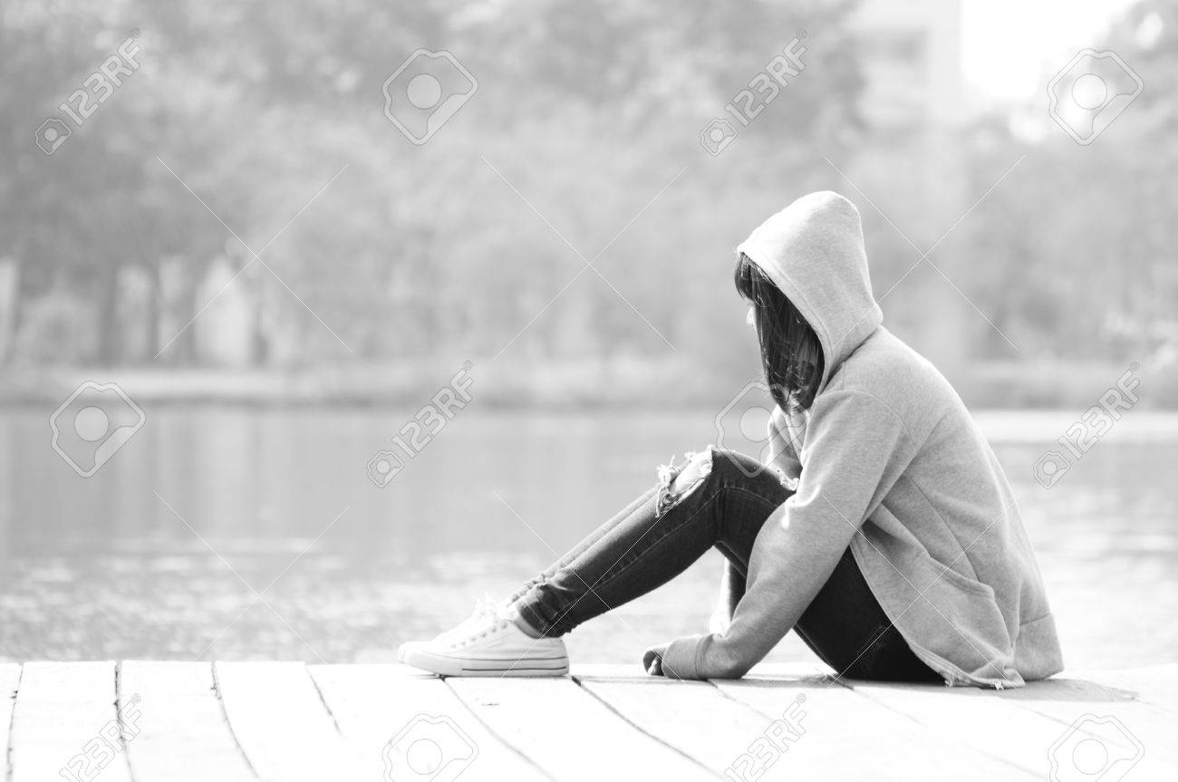 sad teenage girl sitting alone near river stock photo picture and