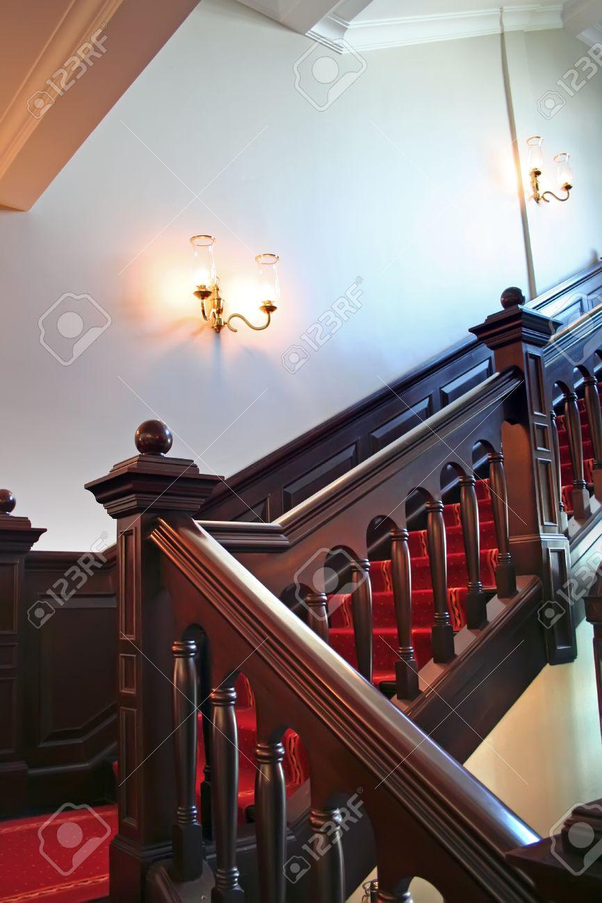 escaleras de madera con las paredes de madera oscuras del blanco de los pasamanos foto de