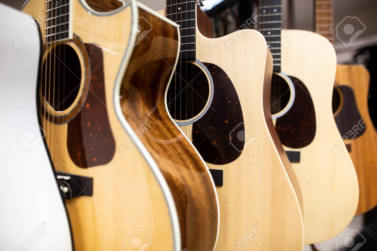 Close up of classic guitar drapped in a row in a huge musical shop, instrument shop, instrument concept - 142061184