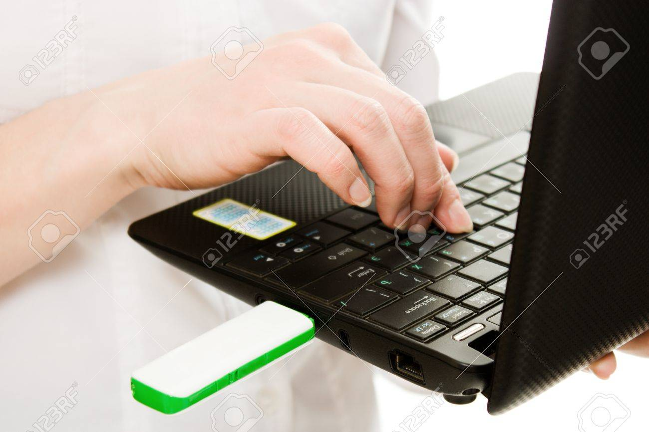 Closeup of plugging in flash drive into laptop computer on a white background. Stock Photo - 12896104