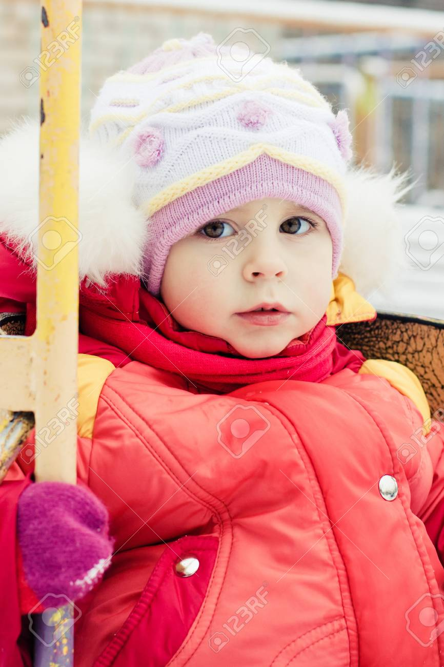 Beautiful happy kid in the red jacket in the winter outdoors. Stock Photo - 16640012