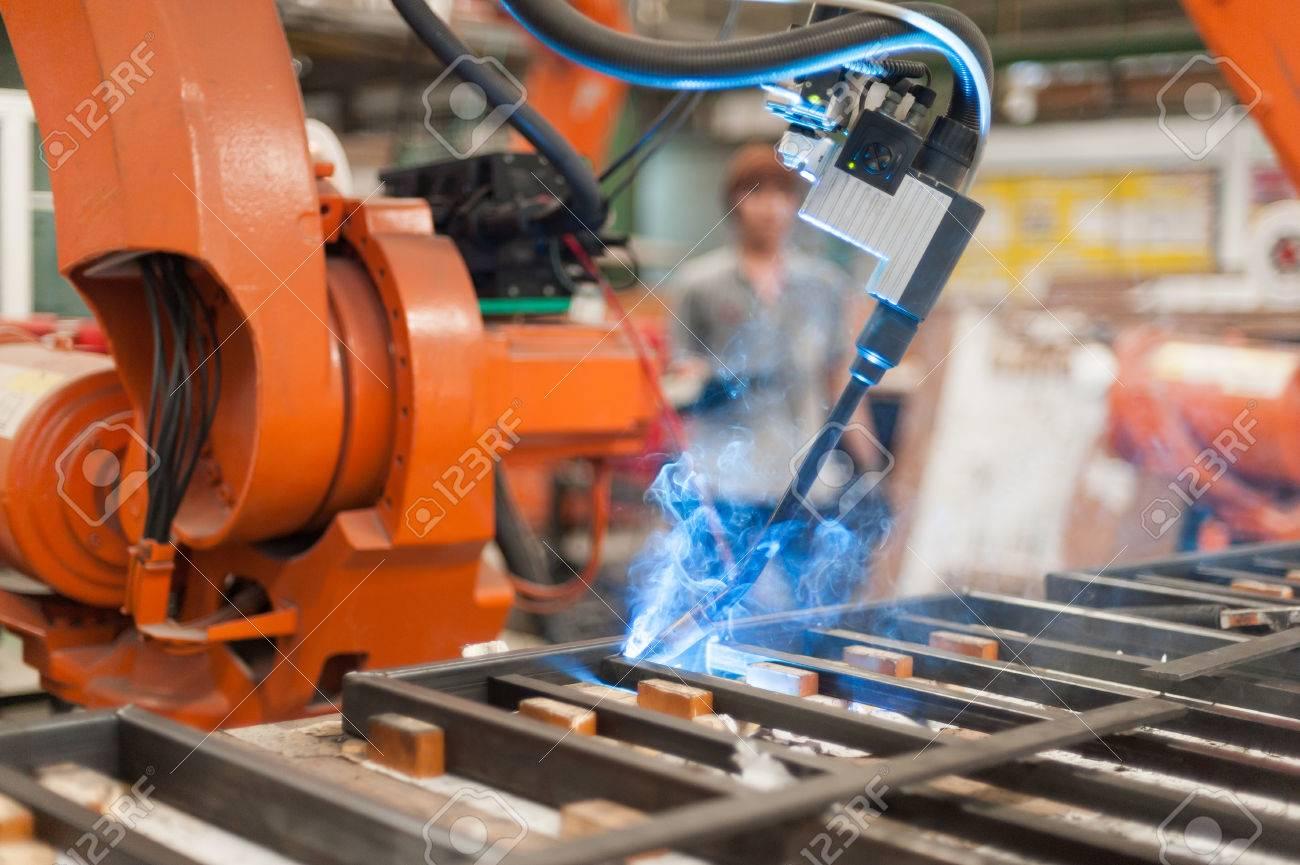 Welder robot operate in steel factory - 58876379