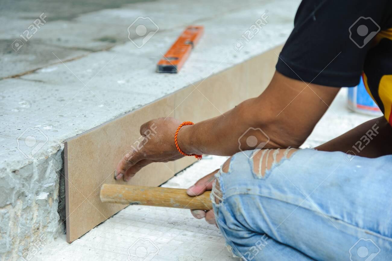 Tiler placing porcelain tile in position over adhesive. Floor tile installation - 148259323