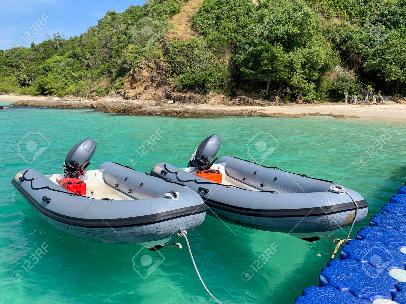 Inflatable boats tie with floating pier in front of a beautiful beach - 160536508