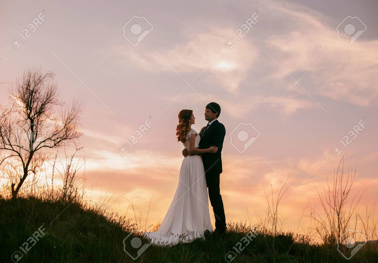 Stock Photo - Stylish wedding on a nature. Walk of lovers at sunset. A beautiful love story. Film colors.
