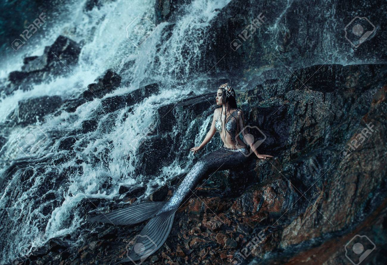 the real mermaid is resting on the ocean shore silver tail