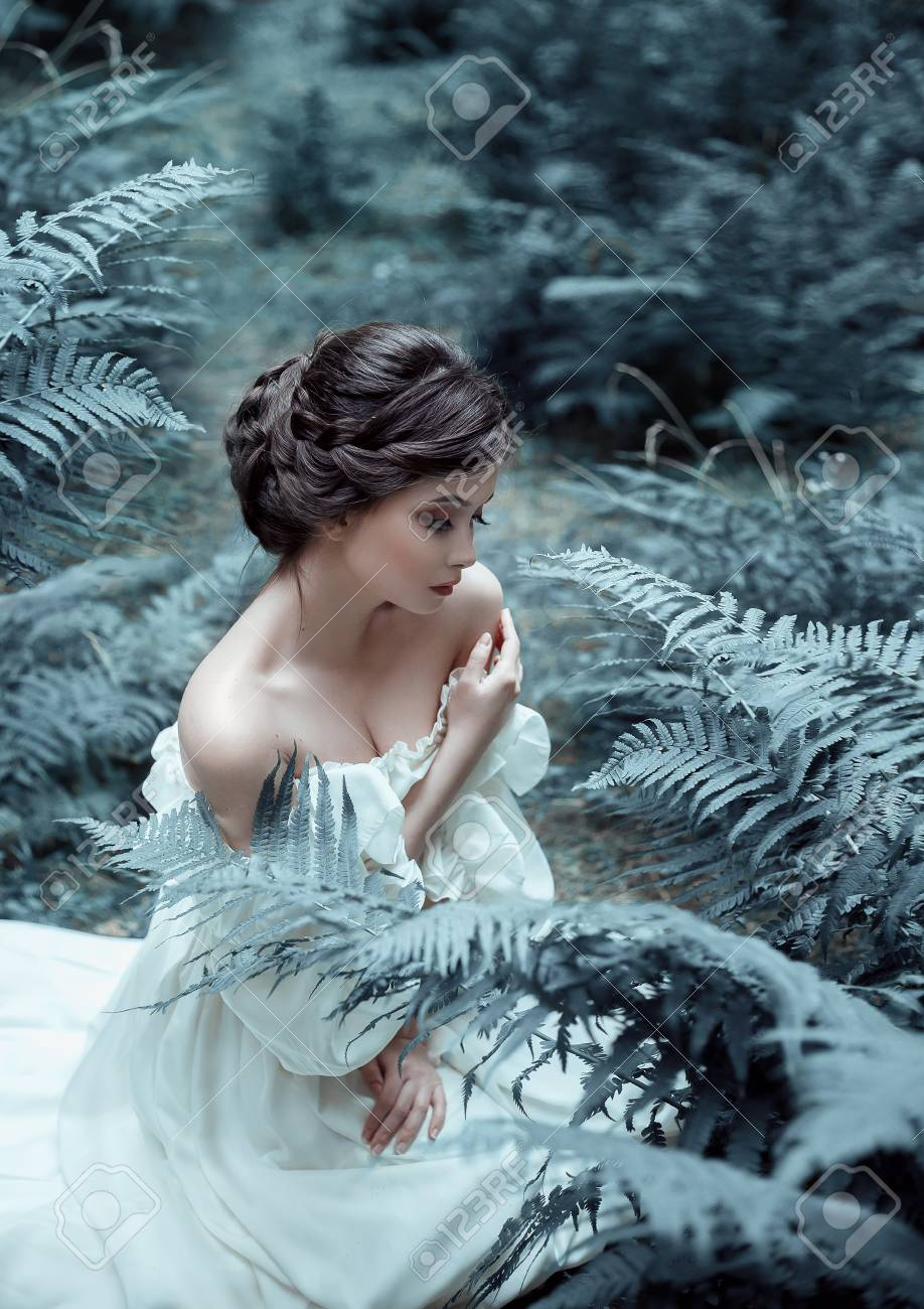 Among the fern and moss an unusual face on the lady is a white vintage dress artistic photography emotions of melancholy and depression