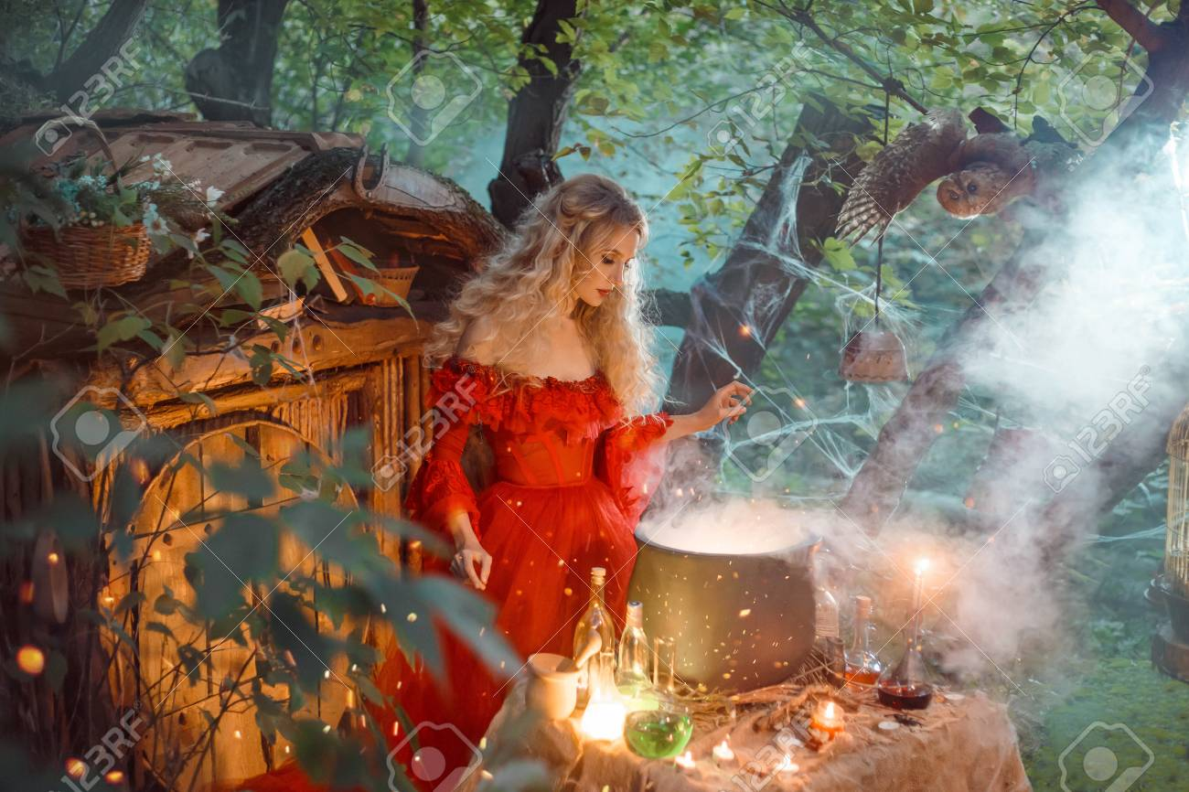 pretty young lady with blond curly hair above big magic cauldron with smoke and bottles with liquids, forest nymph in long bright red dress with loose sleeves prepares potion near wooden house - 119334398