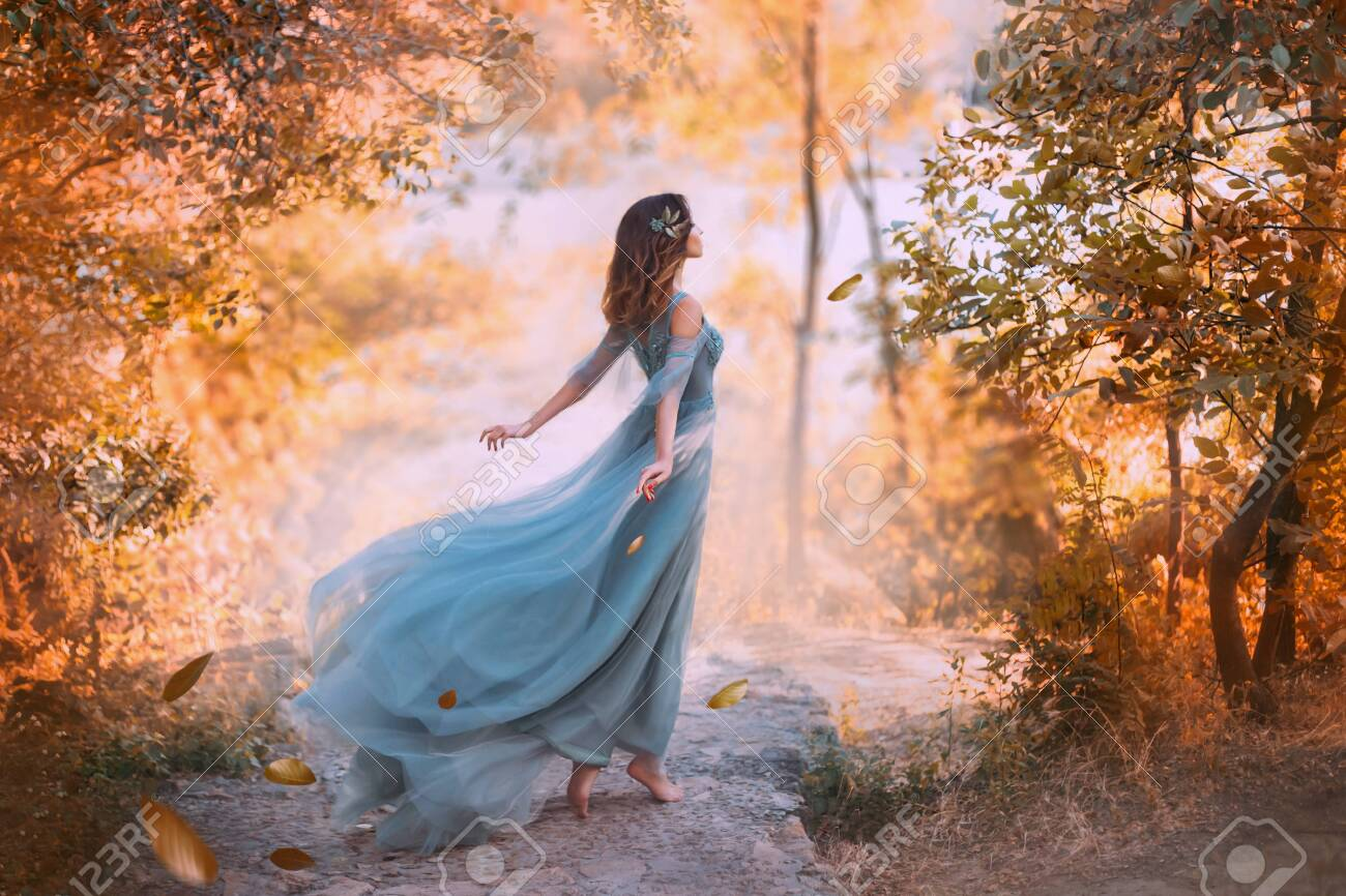 Beautiful woman wearing blue turquoise dress in the forest - 127487610
