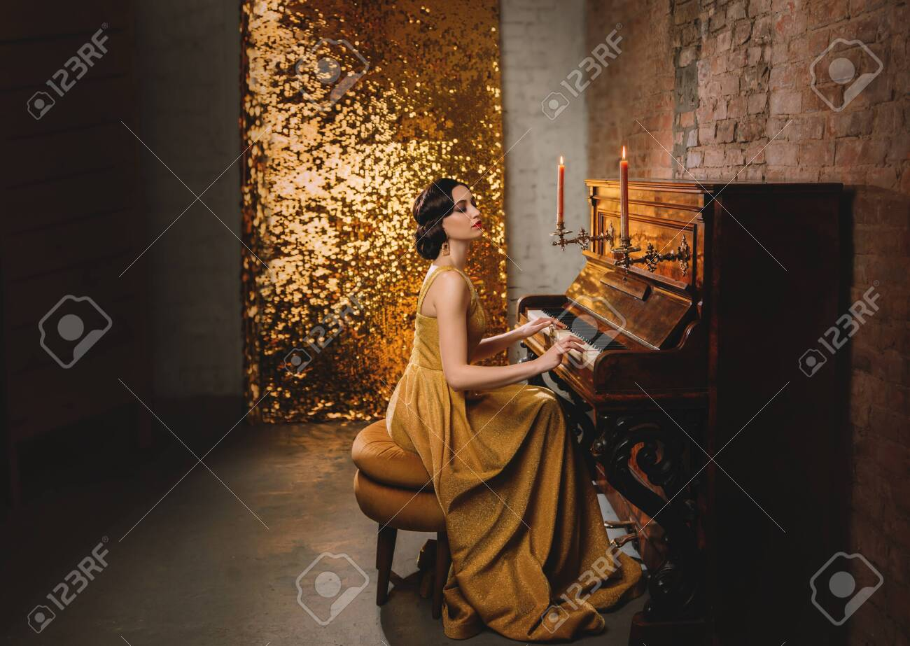 Young woman with finger wave hairstyle gold dress vogue fashion old style 1920 play piano candles romantic burning. Retro Great Gatsby backdrop shine sparkle room brick wall. Musician graduate party - 141943627