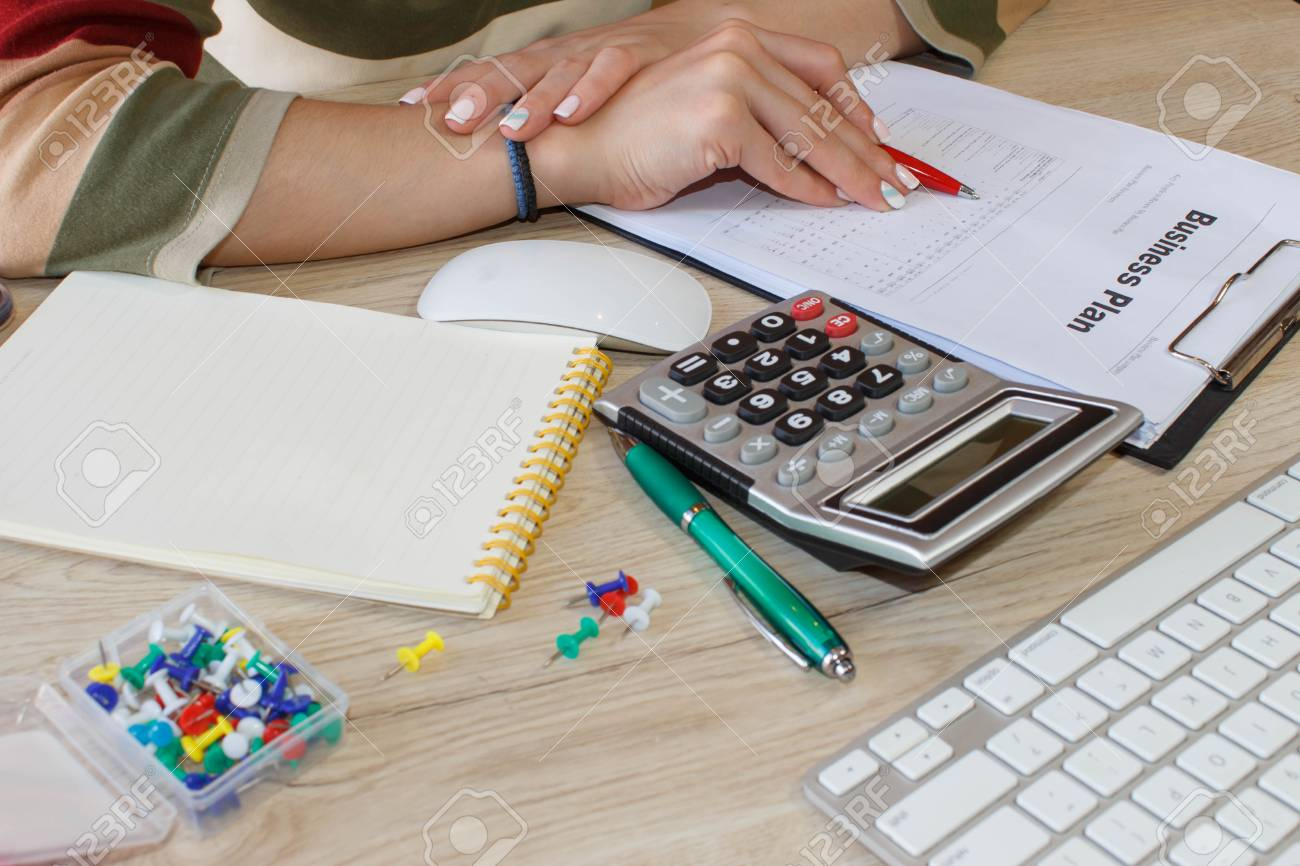 female with business plan calculator and pen on the table young