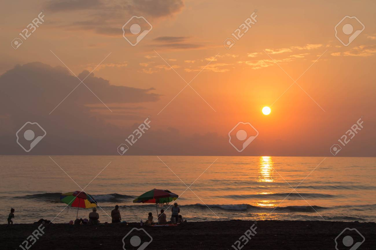 Beautiful Summer Golden Sunset Above With Calm Waves And Reflection