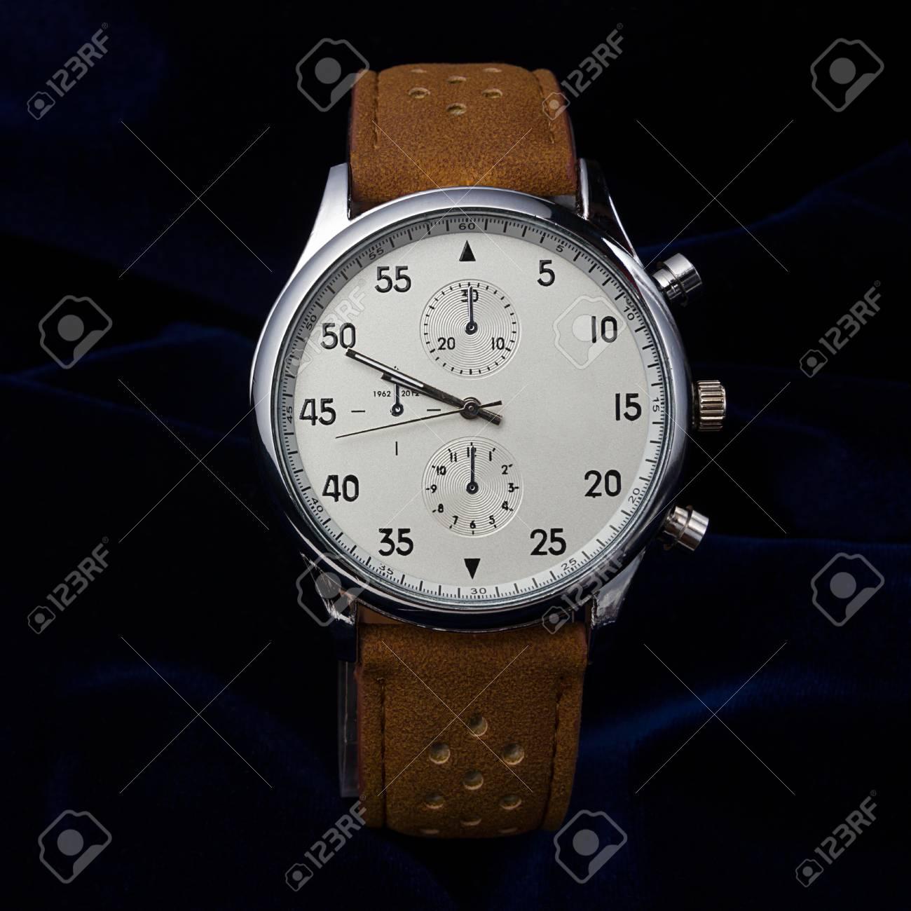 5d13909b9eba Foto de archivo - Reloj de pulsera para hombres con correa de cuero marrón  de cerca sobre un fondo azul oscuro