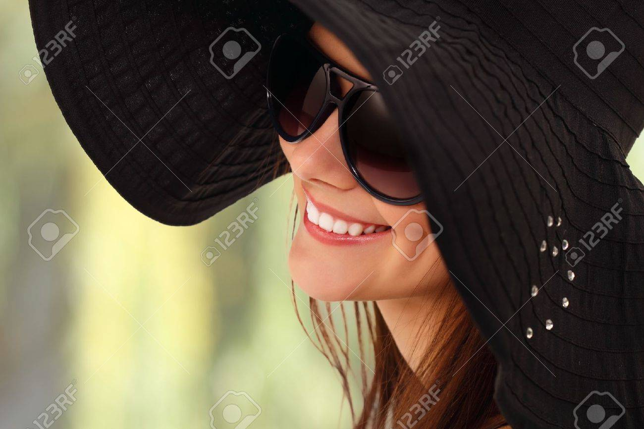 summer teen girl cheerful in panama and  sunglasses enjoying over green nature background Stock Photo - 10460898