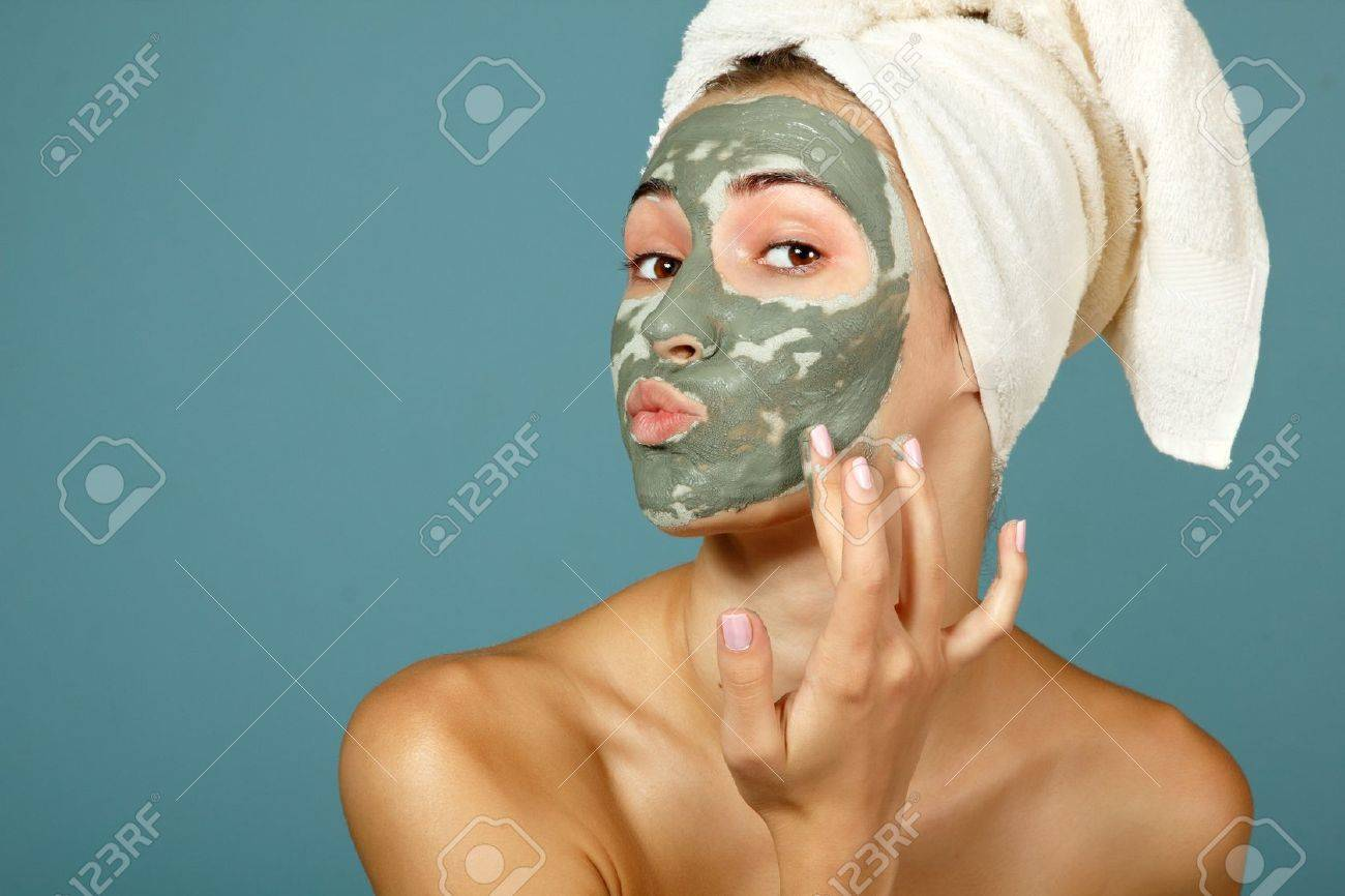 Spa teen girl applying facial clay mask. Beauty treatments. Over blue background. Stock Photo - 16761757