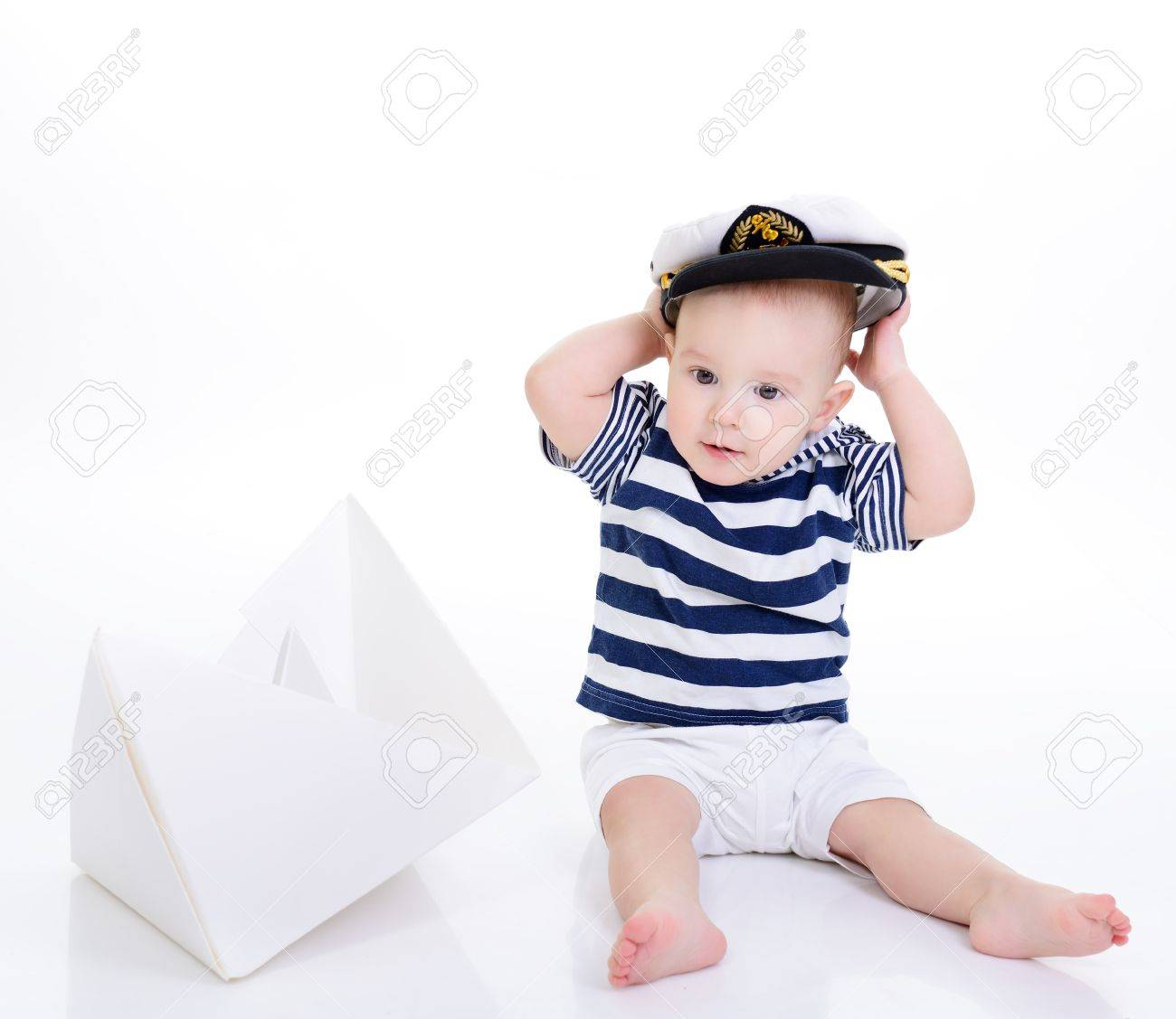 7d3179154 cute baby boy sitting in striped vest with ship of paper and..