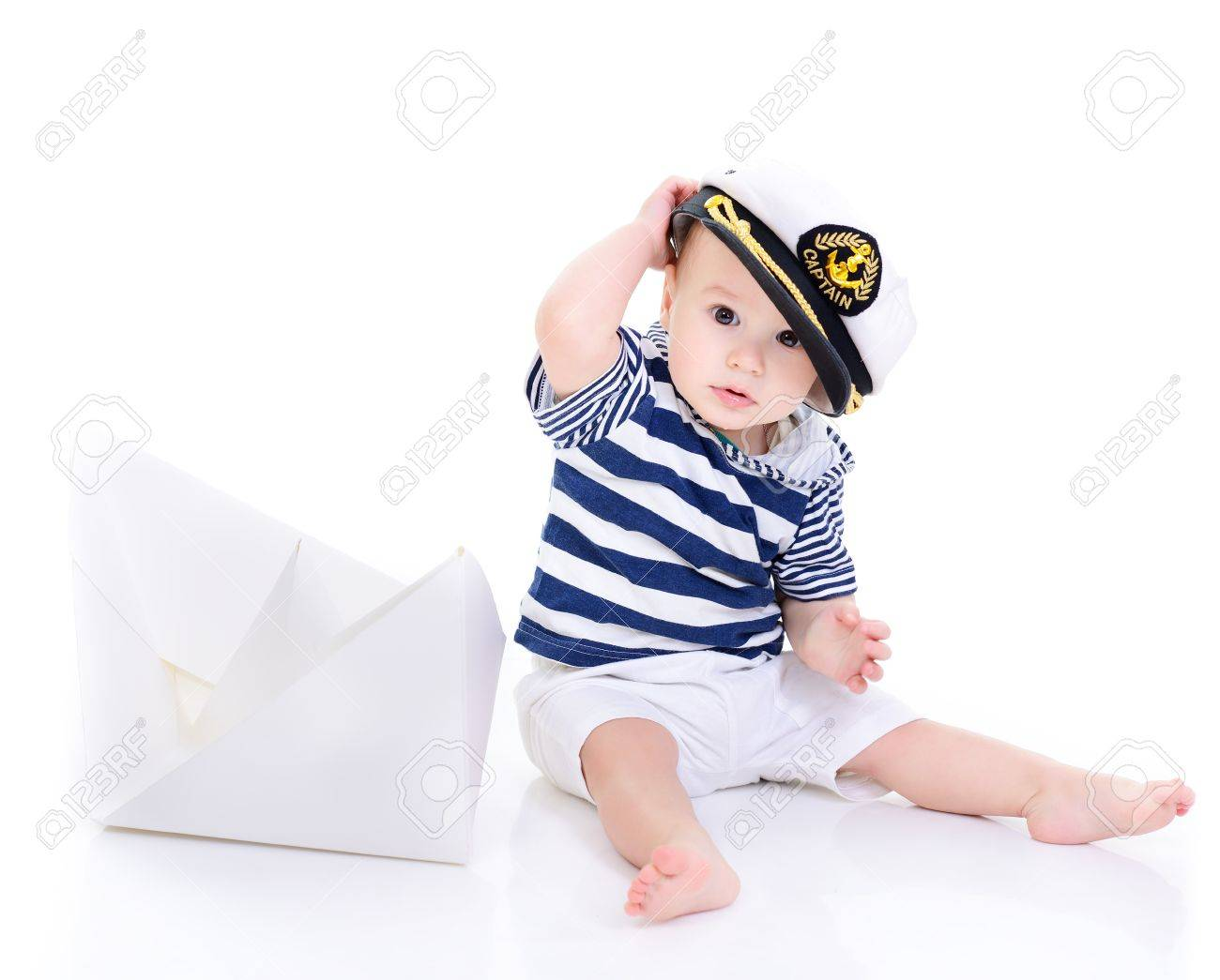 db762059a cute baby boy sitting in captain cap with ship of paper - sailor..