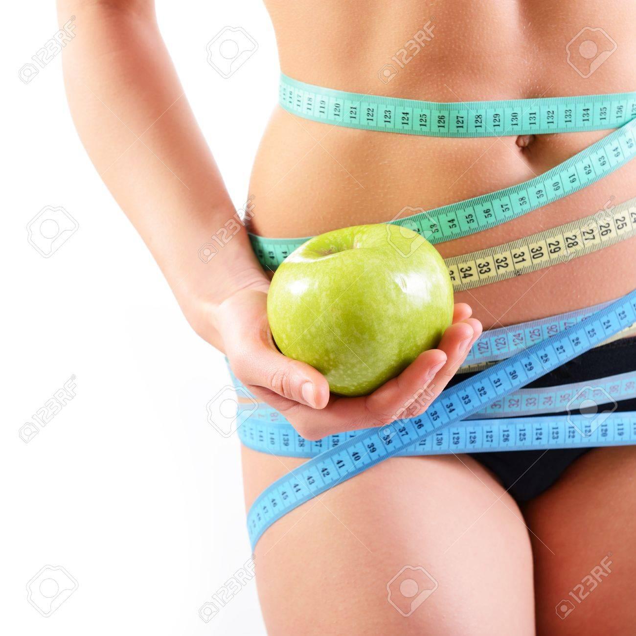 Foto de archivo - Mujer delgada hermosa que sostiene la manzana verde y con  varios colores medición de las cintas en la cintura fe6cfad1d9f2