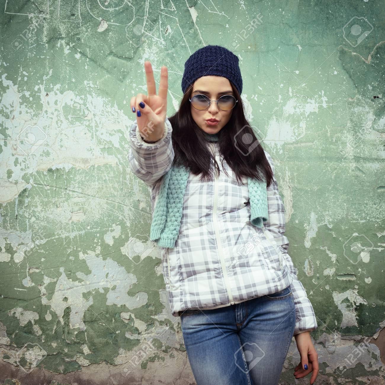 5fbb9c9a9d43a6 Archivio Fotografico - Bella ragazza cool in occhiali da sole e cappello  divertente contro grunge muro di mattoni dà baci, tonica