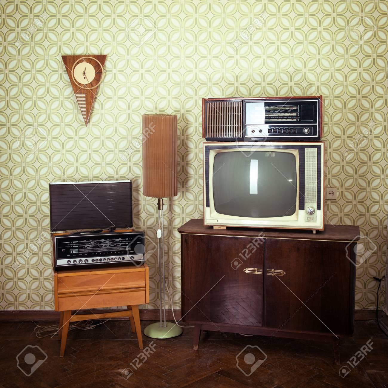 Chambre vintage avec papier peint, téléviseur, fauteuil à l\'ancienne,  lecteur rétro, haut-parleurs, horloges et lampe standart, tonique