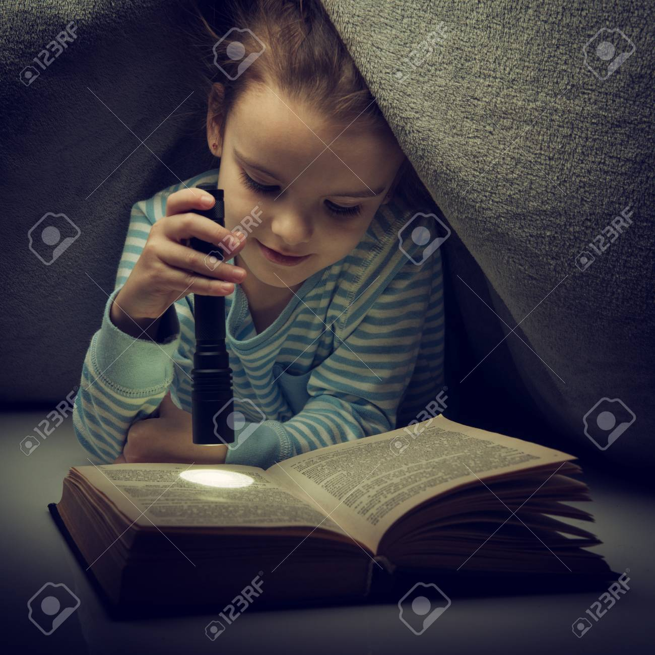 little girl reading fairy tales book under the covers at the.. stock