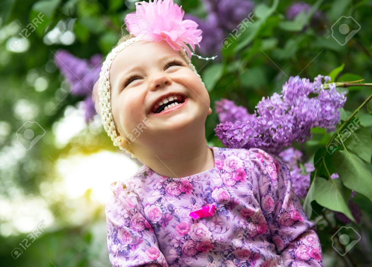 beautiful little girl playing in spring park, lilac flowers garden