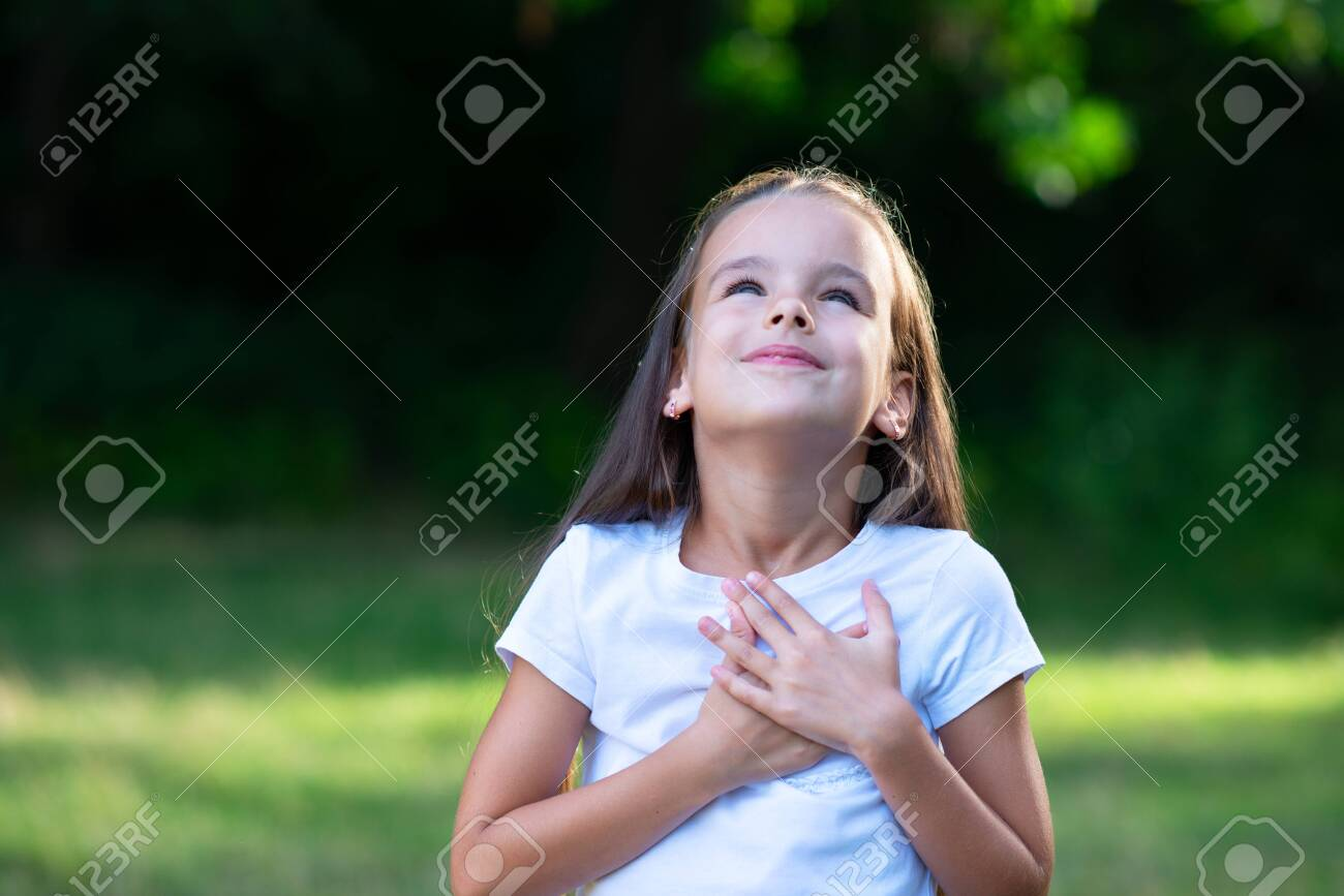 Little Girl Looking Up To At Sky With Hands On Chest Summer Stock Photo Picture And Royalty Free Image Image 128511187