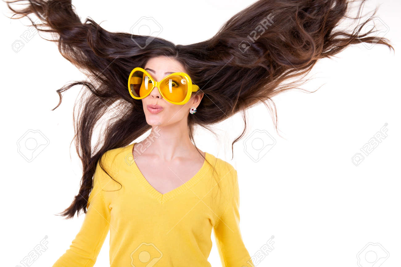 Happy smiling excited comical surprised young attractive woman with long flying hair and big funny yellow glasses isolated on white background. - 166804203