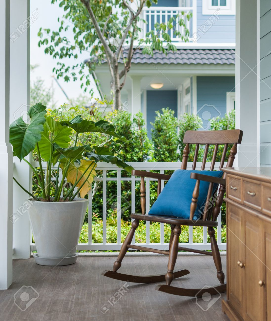 Wooden Rocking Chair On Front Porch With Pillow And Planter Stock