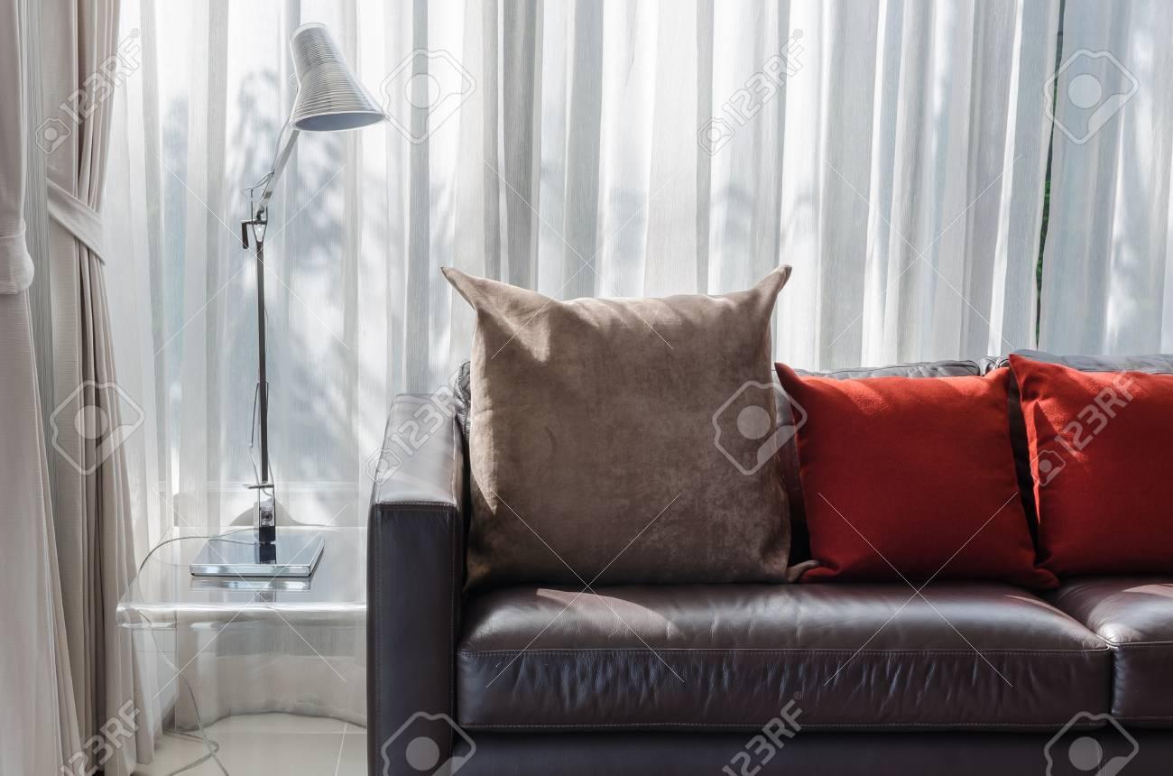 Oreiller marron et rouge sur le canapé avec lampe dans le salon