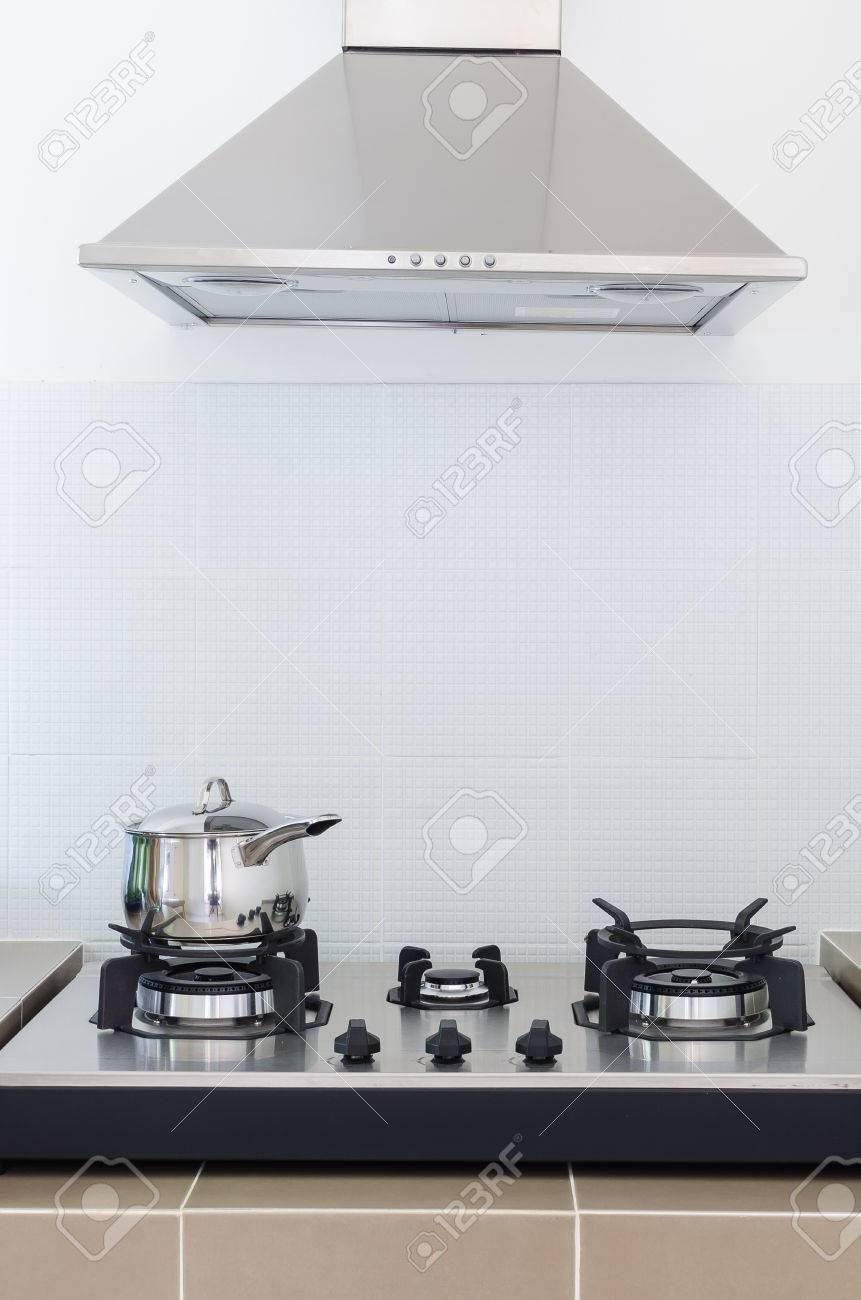 edelstahl pfanne auf gasherd mit abzugshaube in der küche