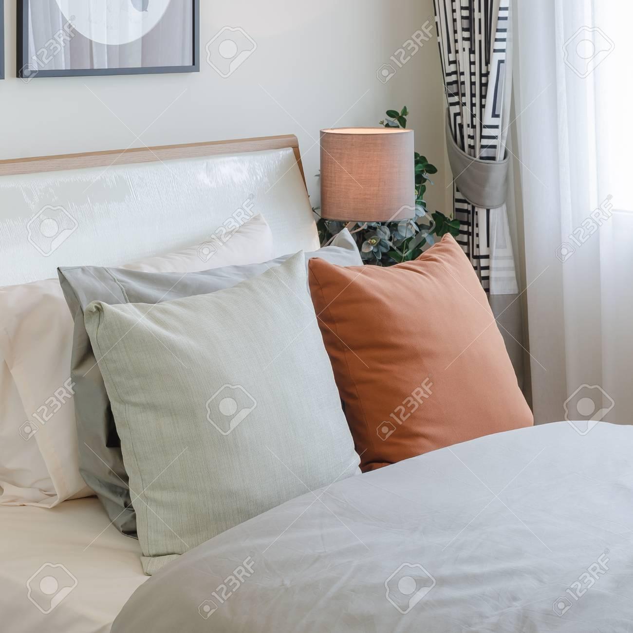 Oreiller de couleur orange sur lit blanc dans la chambre à la maison