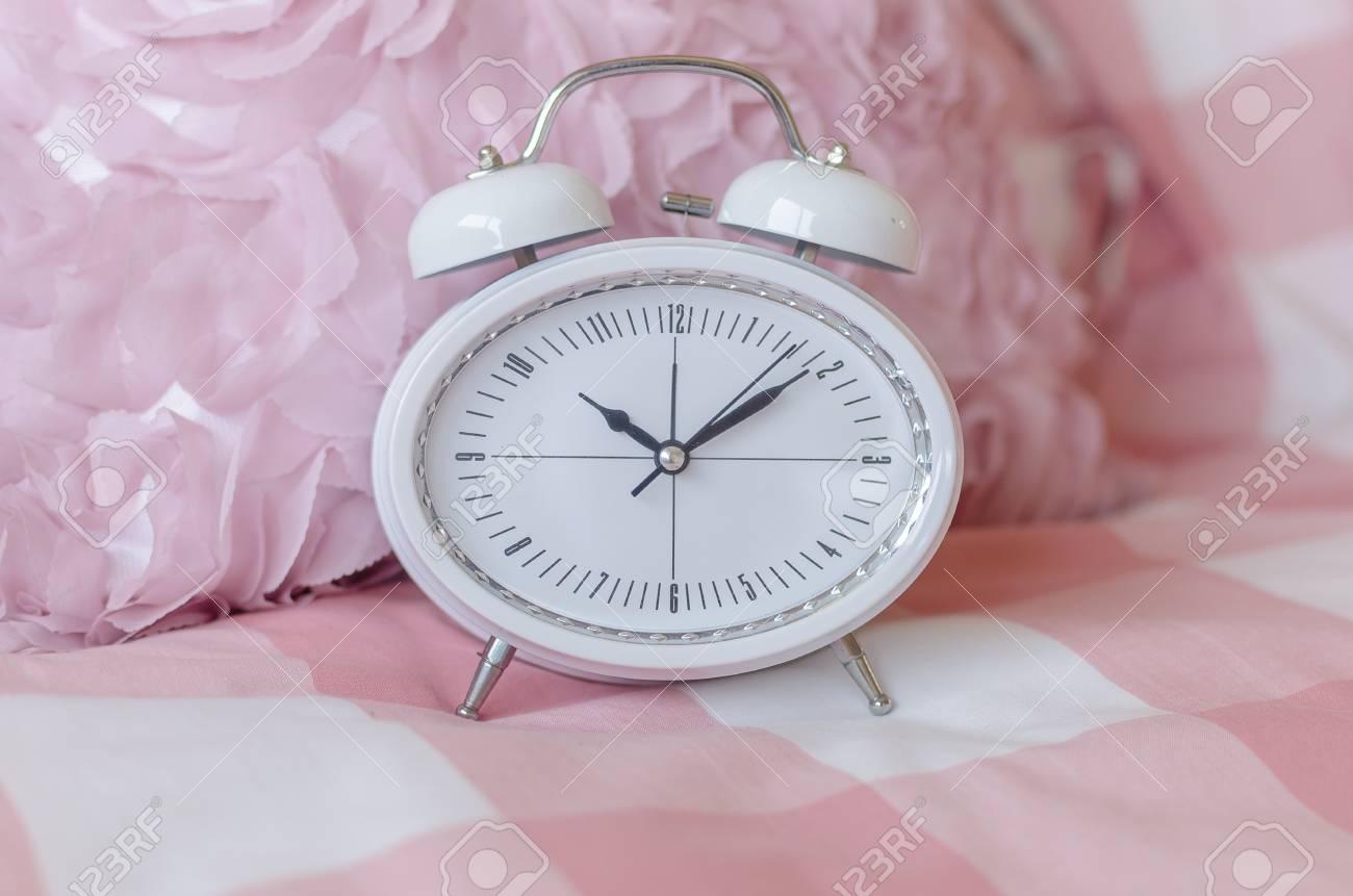 Blanc réveil moderne sur le lit dans la chambre rose