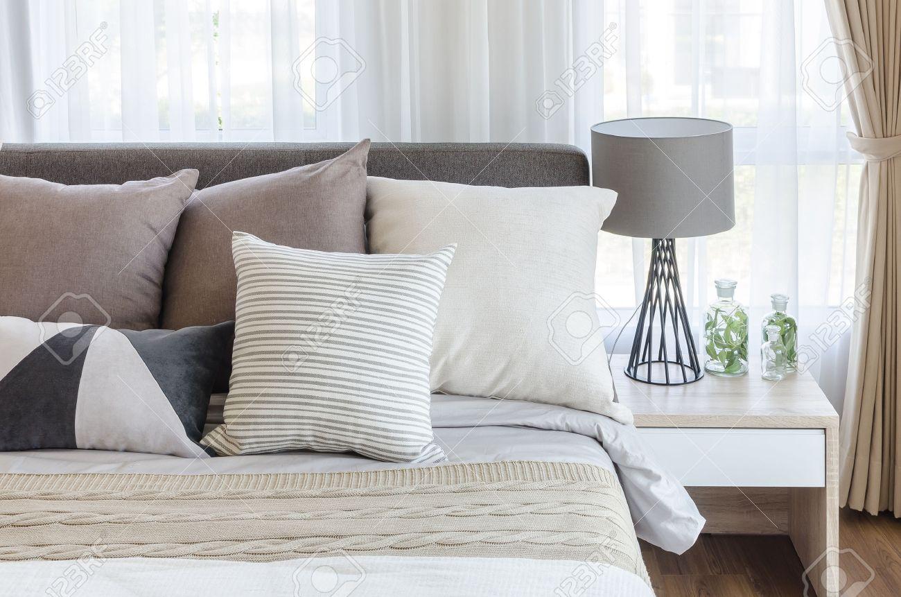 Modern stil sovrum med kuddar på sängen och modern grå lampa på ...