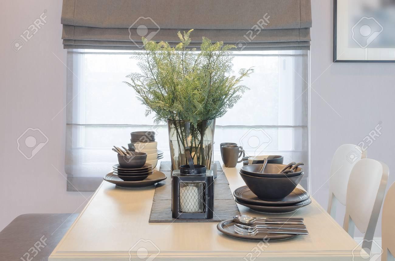 Mesa de comedor de madera con jarrón de cristal de la planta en el comedor