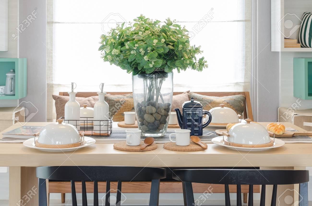 Jarrón de cristal de la planta en la mesa de comedor de madera con silla  negra en el comedor