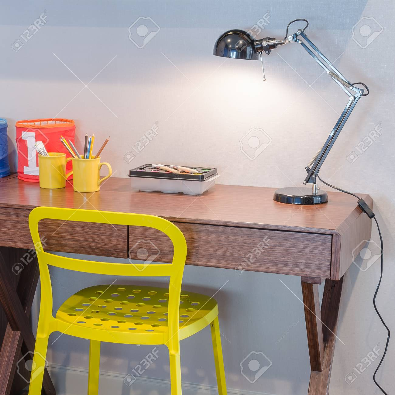 Gelber Stuhl Und Hölzerner Schreibtisch Mit Moderner Schwarzer Lampe