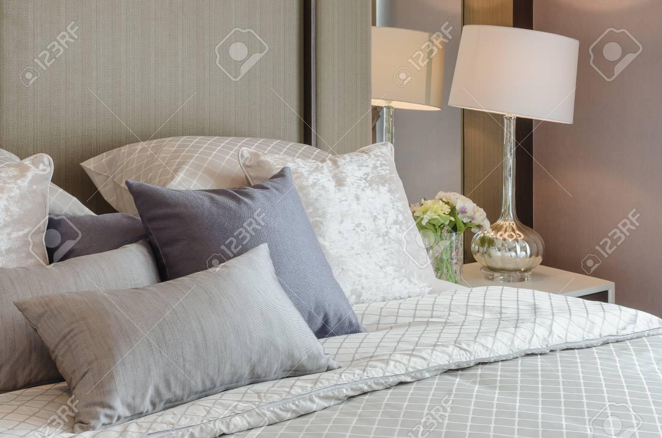 Lampada classica bianca con vaso di vetro di fiori sul lato del tavolo in  camera da letto