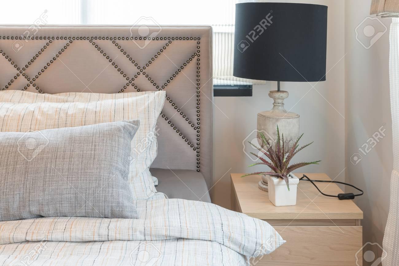 Einzelnes bett im modernen schlafzimmer mit schwarzer lampe und vase