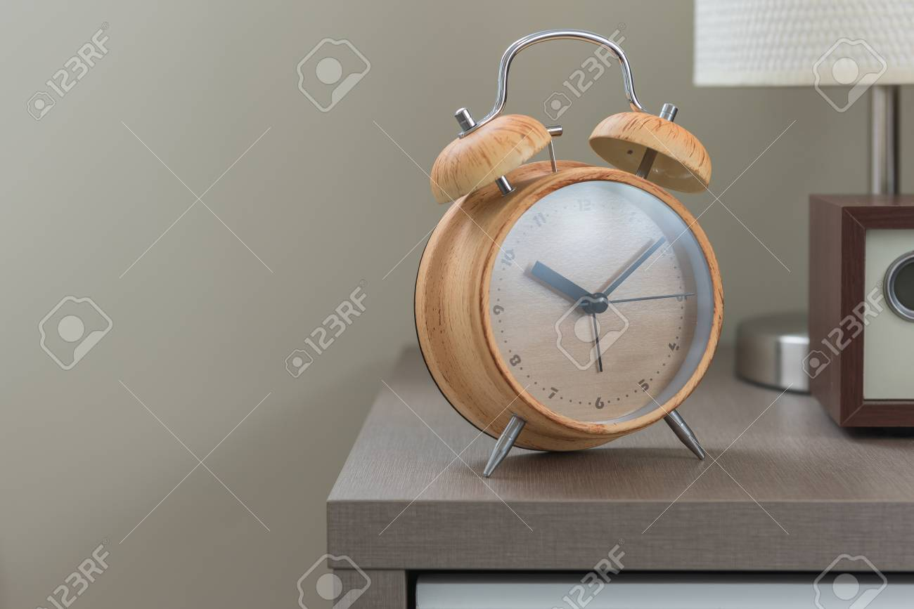 wooden modern alarm clock on bed in modern bedroom design