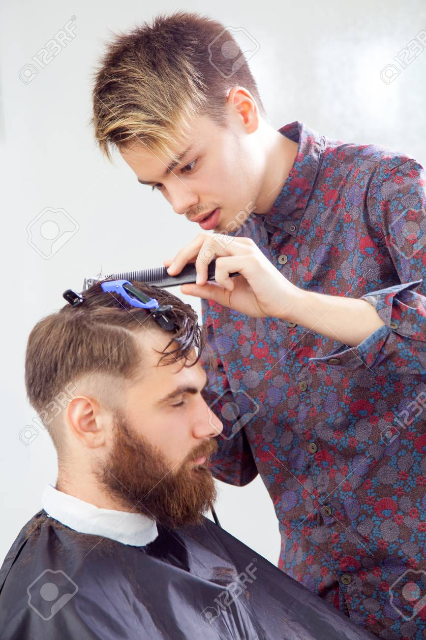 barber cutting hair with scissors and comb. side view of man..