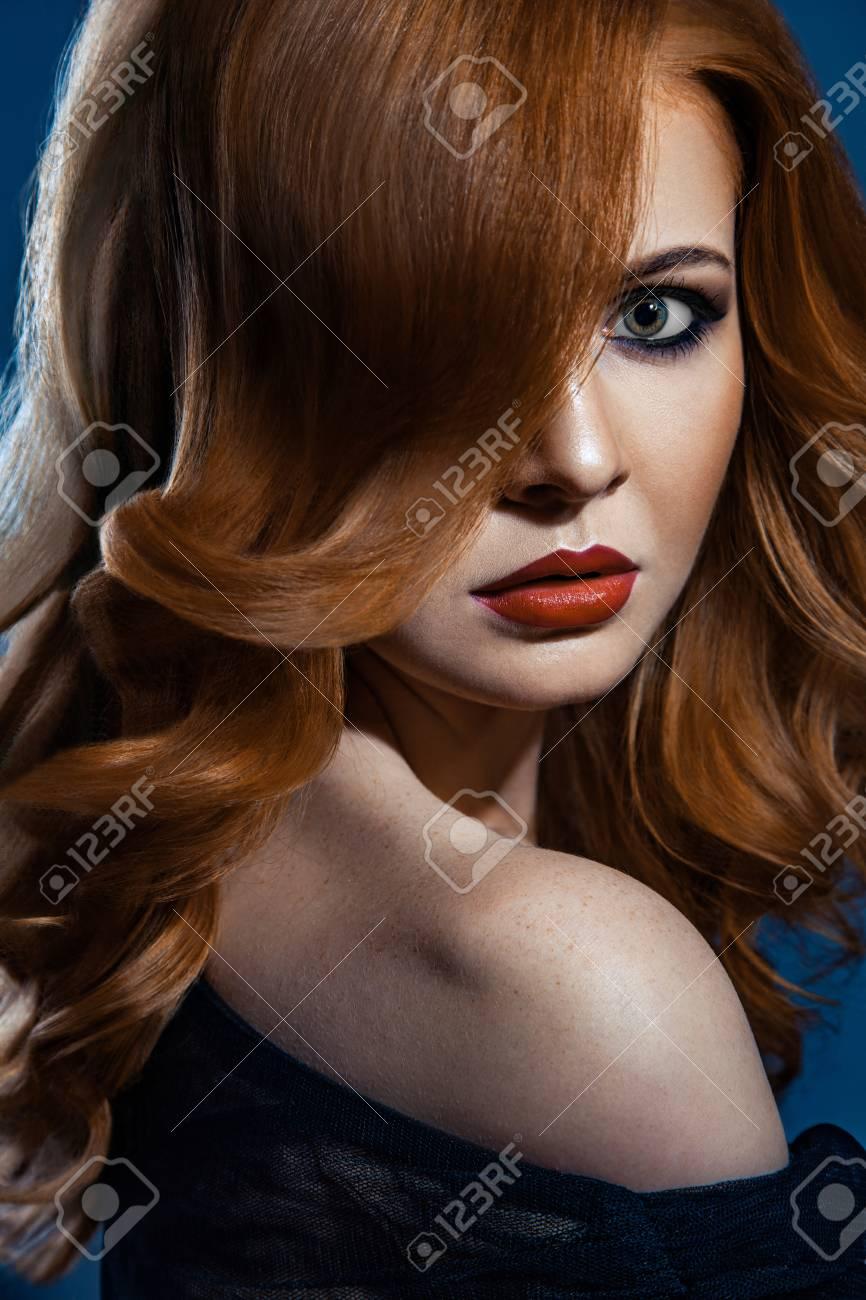 Chica De Moda Hermosa Con El Pelo Largo Y Castaño Ondulado De Color Rojo.  Modelo Rubio Con El Peinado Rizado Y Maquillaje Ahumado De Moda. 8c1fb64cc289