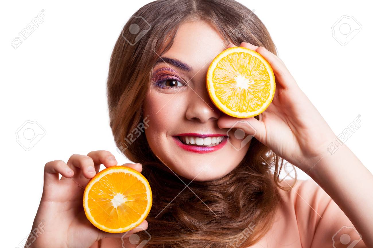 Young beautiful funny girl with orange slice and makeup and hairstyle
