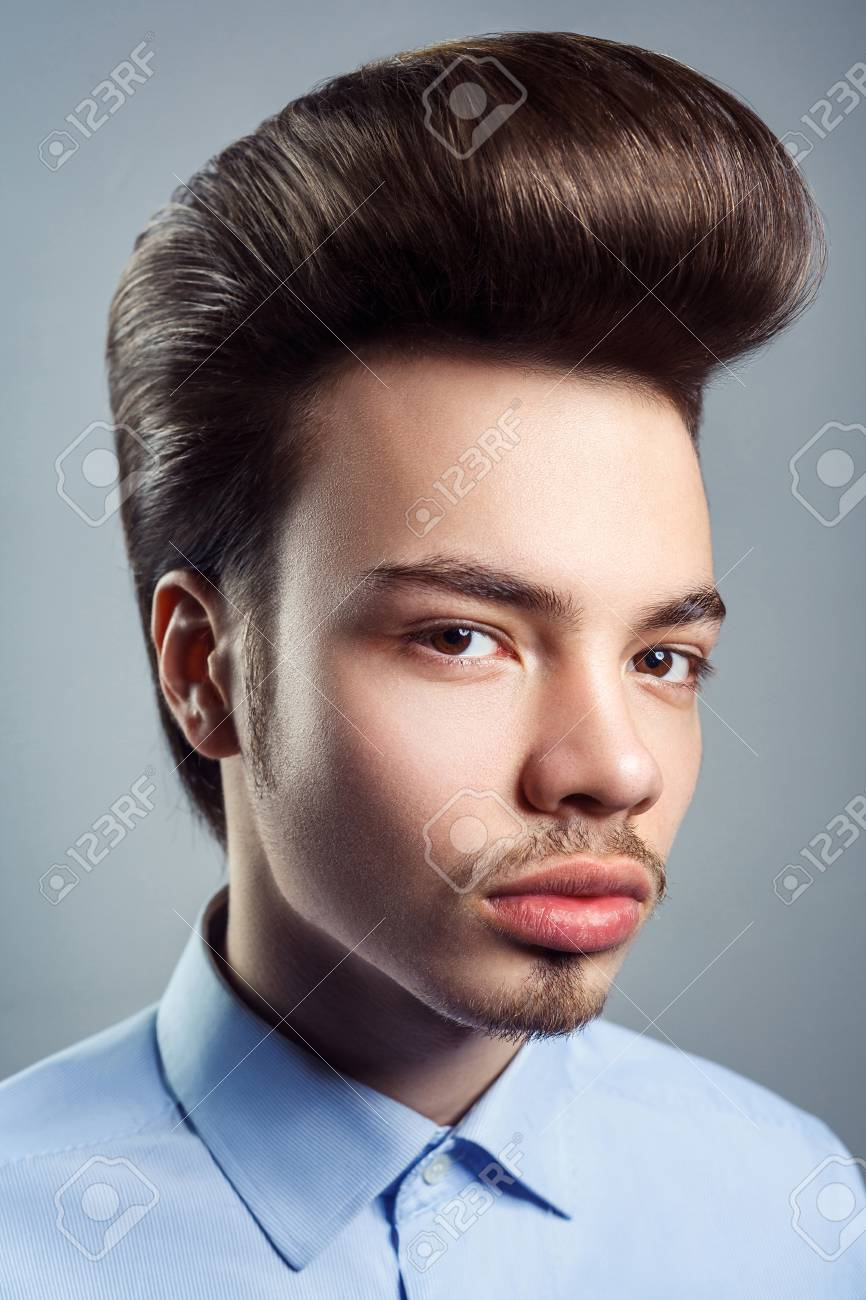 Portrait of young man with retro classic pompadour hairstyle...