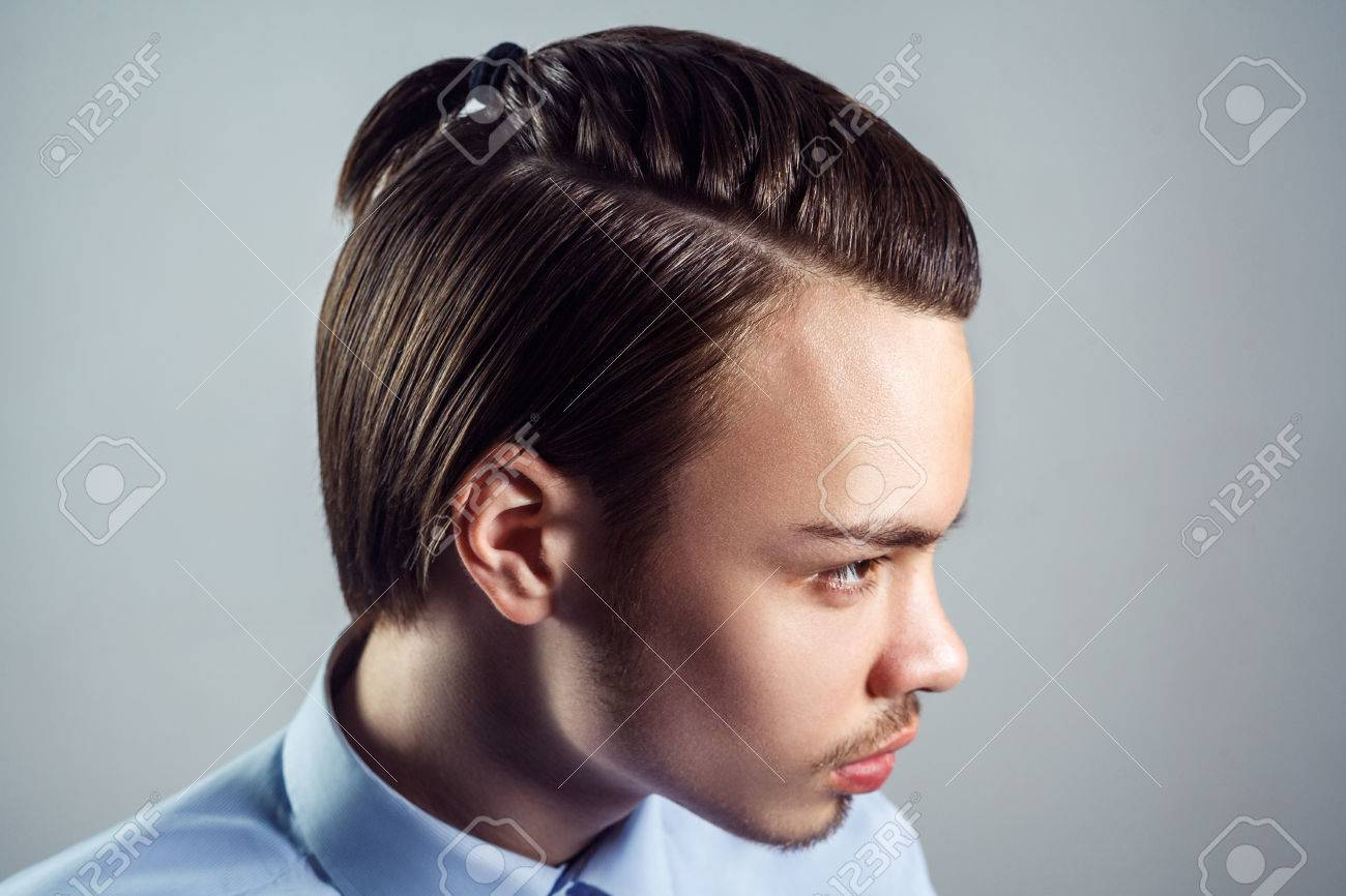 Side View Portrait Of Young Man With Top Knot Hairstyle. Studio Shot. Stock  Photo