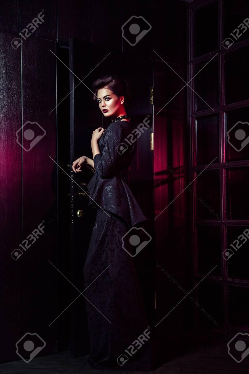 6d6a247e21 Il ritratto di bello modello di moda in vestito nero classico, trucco e  acconciatura vicino alla porta scura che sta e che posa e luce rossa dalla  ...