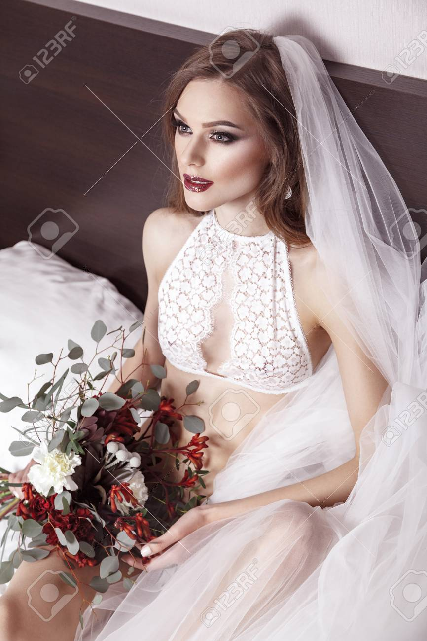 View from above beautiful brunette woman in bridal underwear stock photo view from above beautiful brunette woman in bridal underwear girl sitting in bed holding flowers and looking forward studio shot junglespirit Choice Image