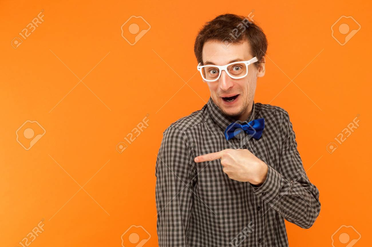 ea20d3014 Foto de archivo - Hombre en gafas blancas mirando a cámara y apuntando el  dedo en el espacio de la copia. Estudio de disparo. Aislado en fondo naranja