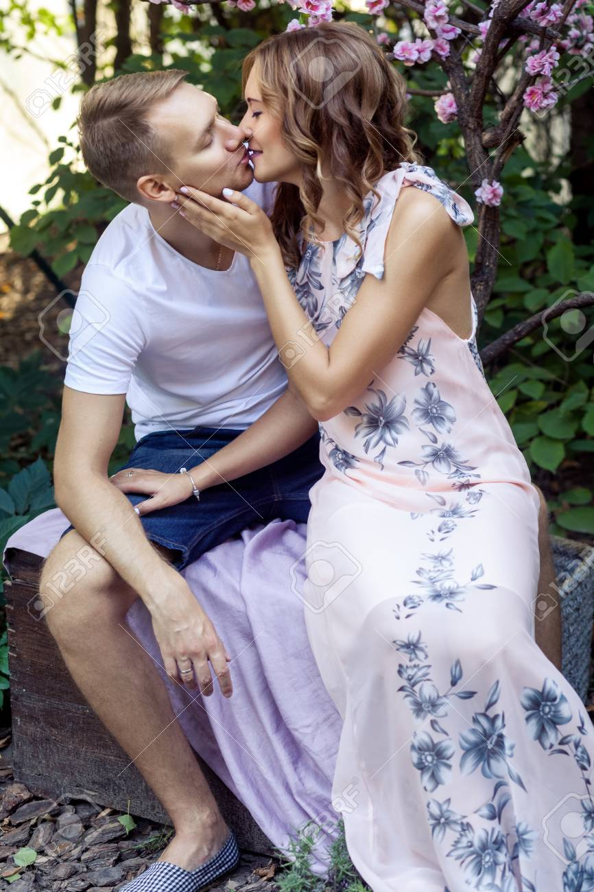 passionate kiss of a lovely couple in the park outdoor shot